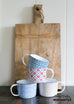 wooden cutting board with floral enamel mugs