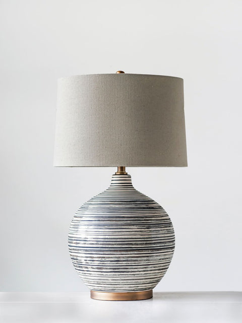 gray and cream striped ceramic lamp with natural linen shade
