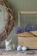 wooden tool caddy with lavender bundles and small bunny statue with ceramic robin eggs