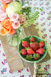rustic wooden cutting board with bowl of strawberries