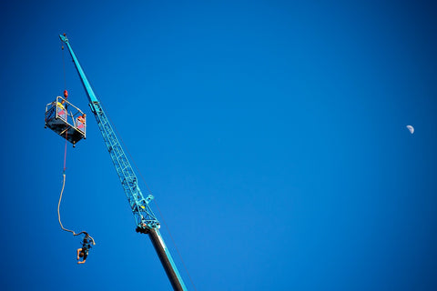 Bungee jumper from a crane with a snowboard against a clear blue sky