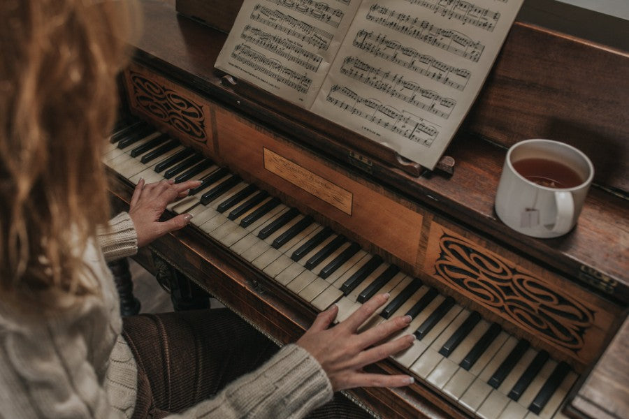 Girl playing the piano with a cup of tea in a Barton Croft mug