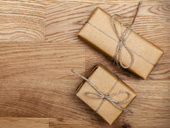 Two brown gift packages with bows tied around them.