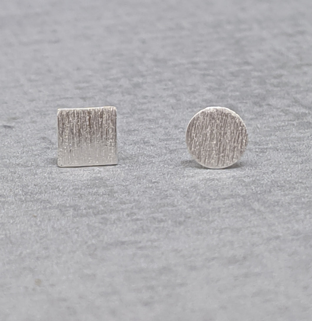 Mismatched square and round sterling silver studs with brushed finish
