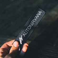"AutoNirvana ""Remove Before Flight"" keychain held up"