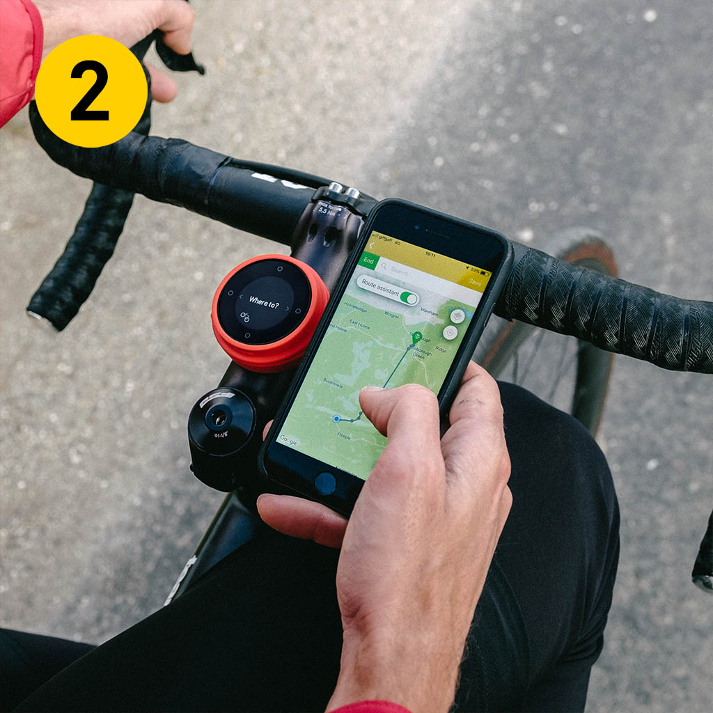 a man planning his cycle route on his phone on his black bicycle