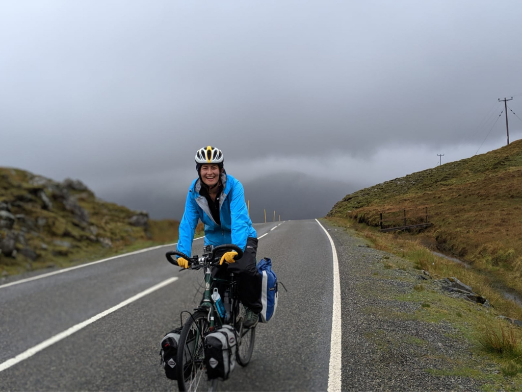 Lucy cycling in rainy Scotland countryside