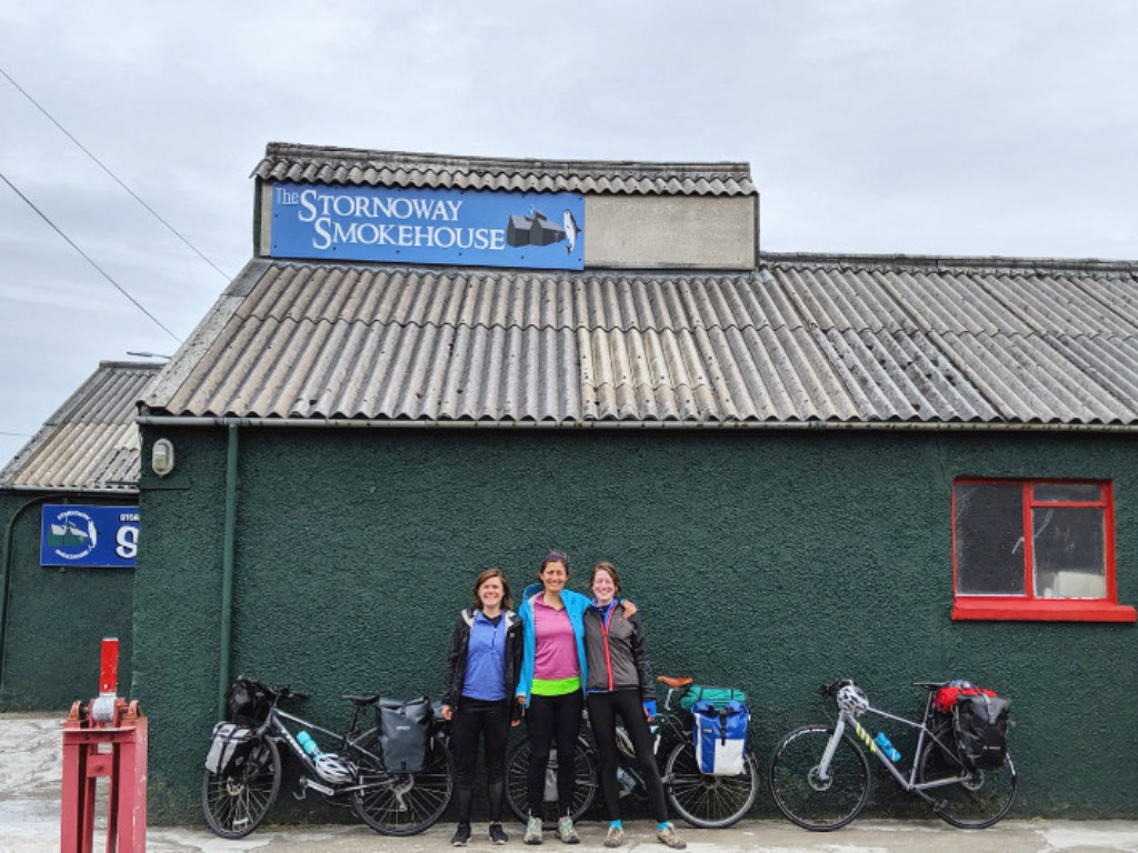 Fiona, Lucy and friend standing outside a building in Stornoway with their bikes