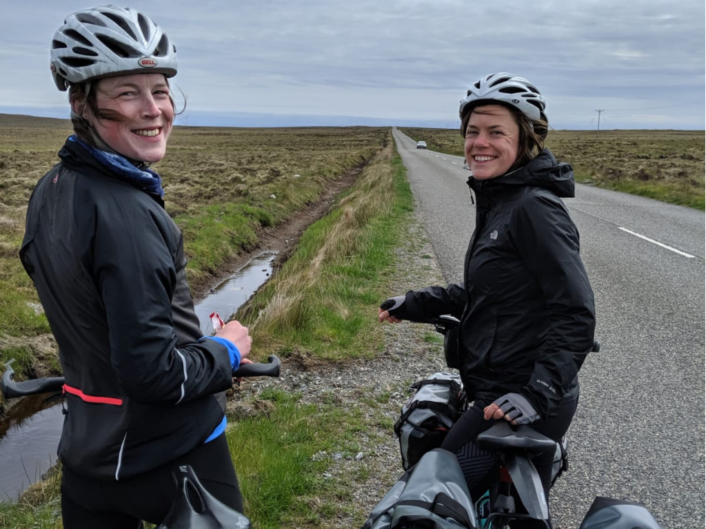 Fiona and friend on bikes looking back at camera in Scottish countryside