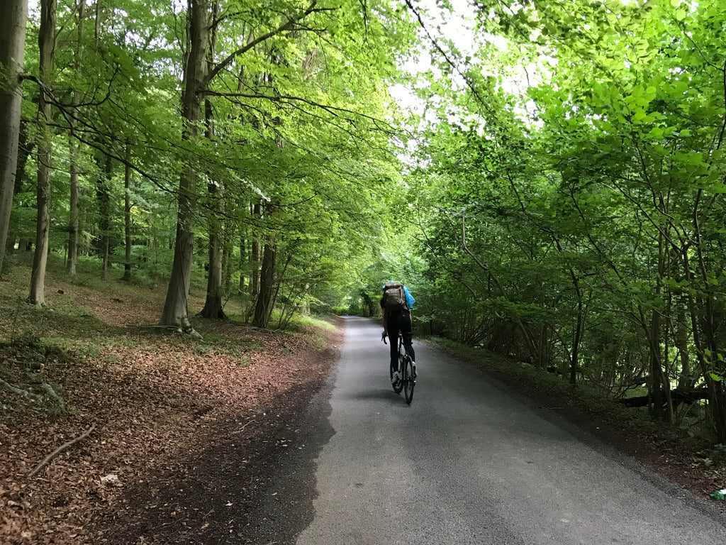 kate cycling through a forest