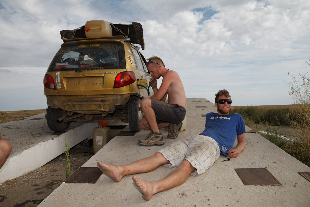 Sam and a friend repairing a car in Australia