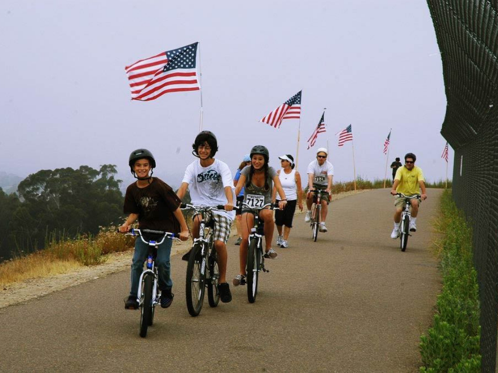 Kids riding on bicycles with American flags