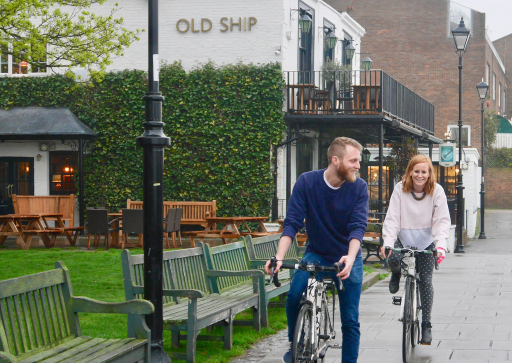 Sam and jayne cycling in front of the old ship pub in Chiswick