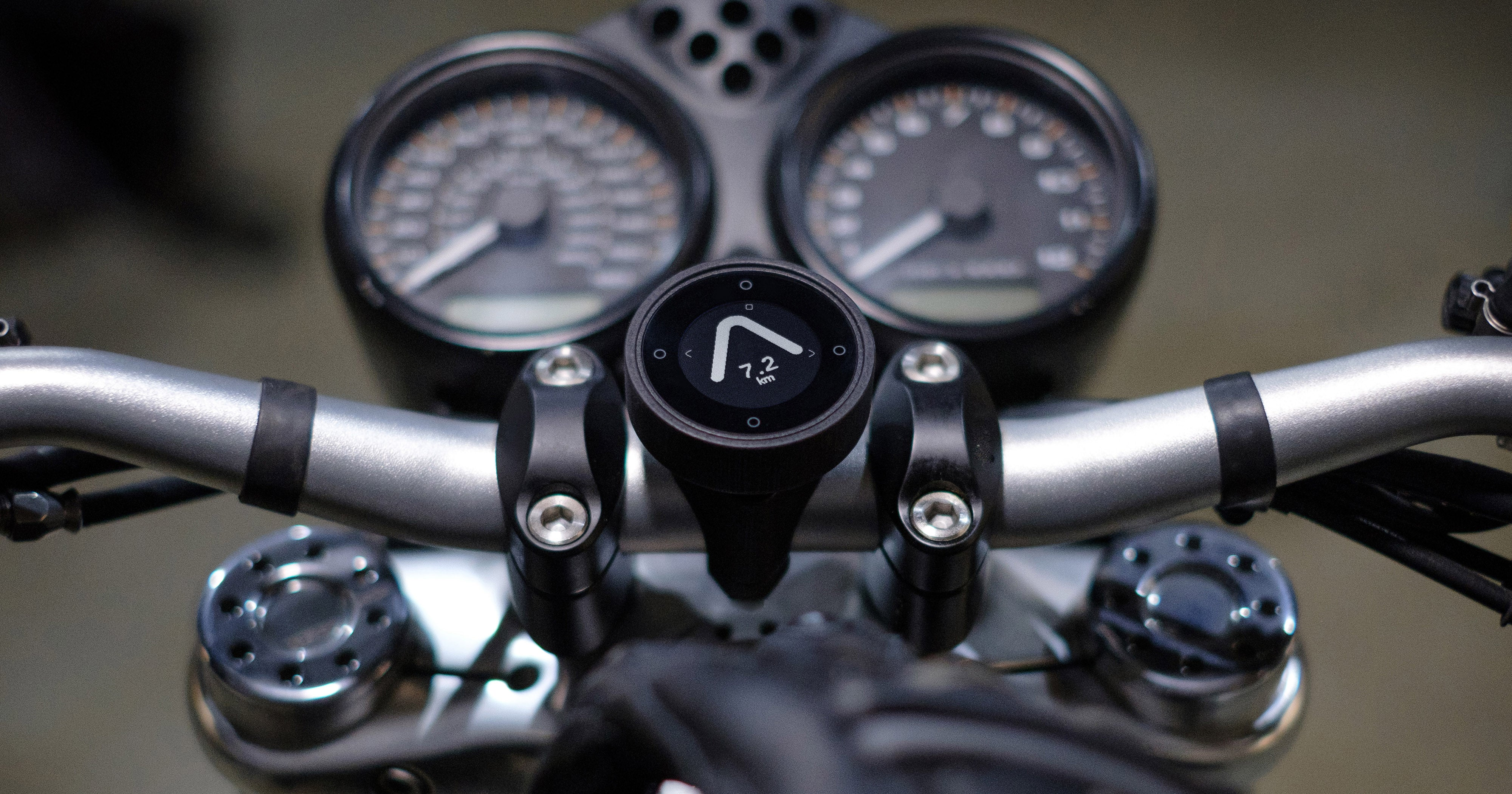 a motorcycle sat nav attached on the handlebars of a motorbike showing the direction