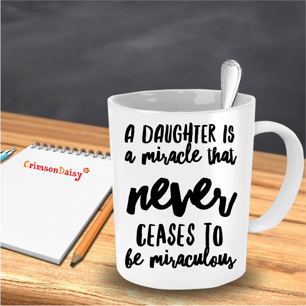 A Daughter is A Miracle that Never Ceases to be Miraculous Coffee Mug in the table