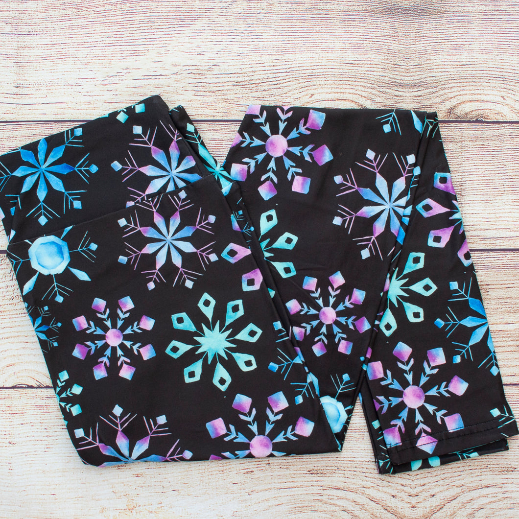 This legging print is a black backdrop with blue and purple watercolor snowflakes of various shapes and sizes. You'll be rocking Queen Elsa's vibe.