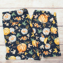 Navy backdrop with hand drawn white yellow and orange pumpkins, gold brown and green fall leaves, and small golden flowers. Festive and appropriate for the entire Fall season through Thanksgiving.