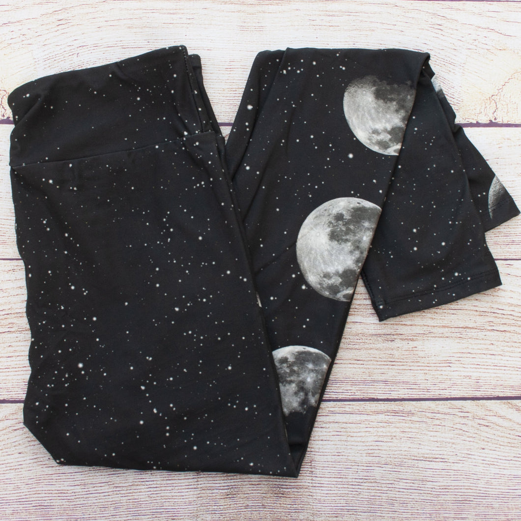 buttery soft leggings printed black with star dots like the night sky, the (photo real) phases of the moon running down the side of one leg