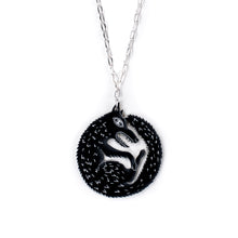black wolf necklace on white background