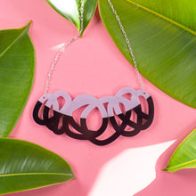 Load image into Gallery viewer, Chunky black & lilac statement necklace on pink background with green leaves