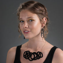 Chunky black statement necklace on model