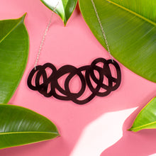 Chunky black statement necklace on pink background with green leaves