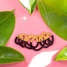 Load image into Gallery viewer, Chunky black and wood statement necklace over pink background with green leaves