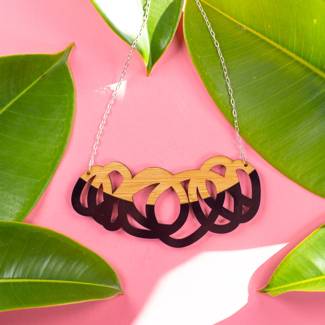 Chunky black and wood statement necklace over pink background with green leaves