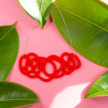 Load image into Gallery viewer, Chunky red statement necklace on pink background with green leaves