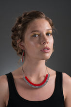 silver and red necklace on model