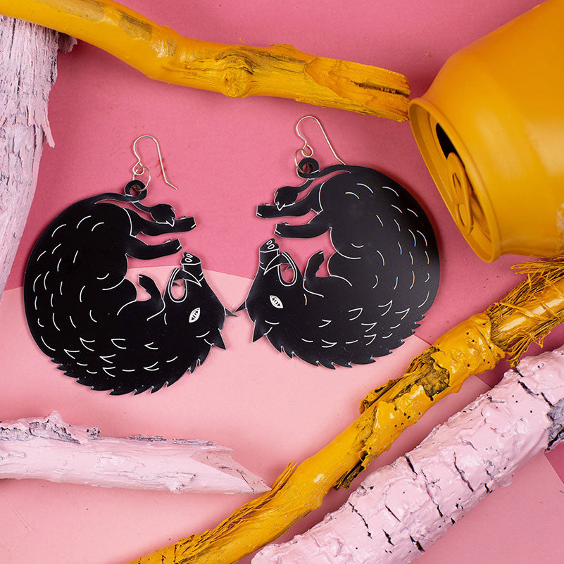 large black boar earrings styled over pink background