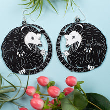 Load image into Gallery viewer, large possum earrings over blue background with plants