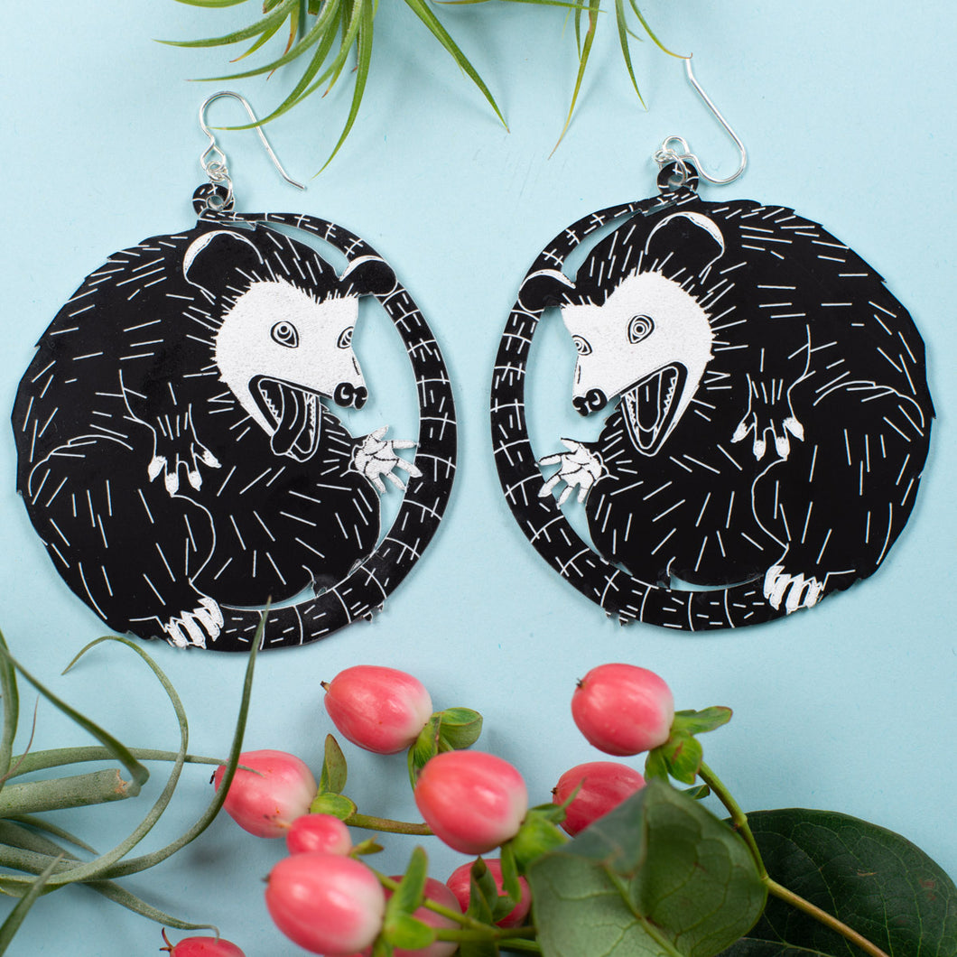 large possum earrings over blue background with plants