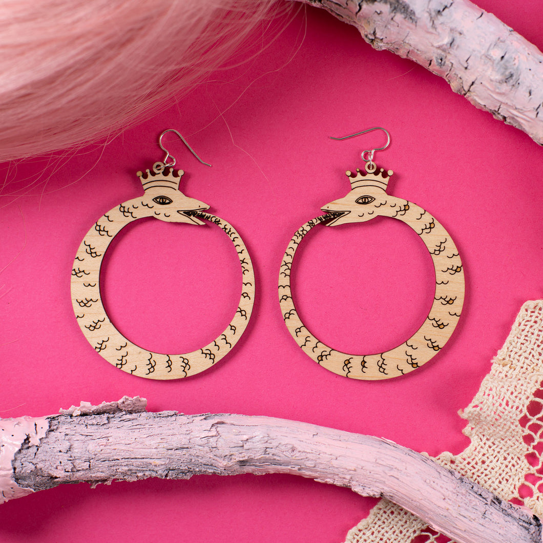 large wood ouroboros earrings over pink background