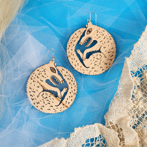 large wood wolf earrings on blue background