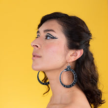 large black ouroboros earrings on model