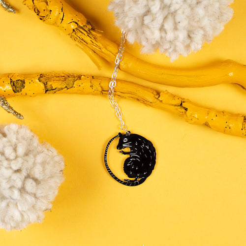 rat necklace on yellow background