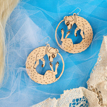 small wood dog earrings on blue background