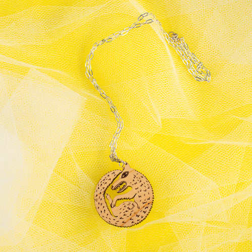wood wolf necklace on yellow background