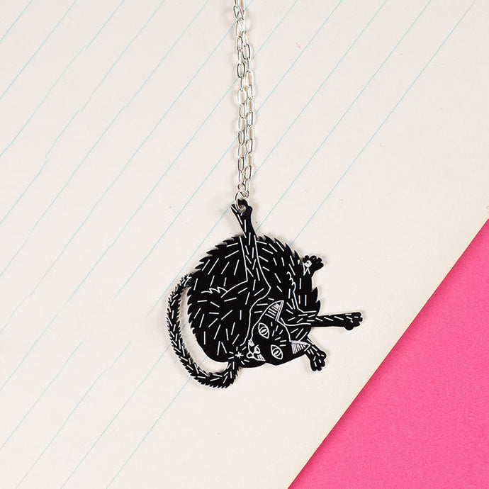 black cat necklace styled on notebook paper