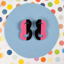 Load image into Gallery viewer, Black and Pink statement stud earrings on polka dot background