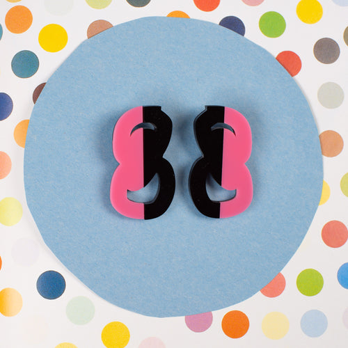 Black and Pink statement stud earrings on polka dot background