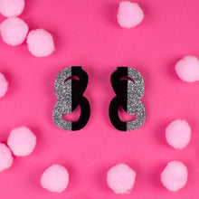 Load image into Gallery viewer, black and silver statement stud earrings on pink background