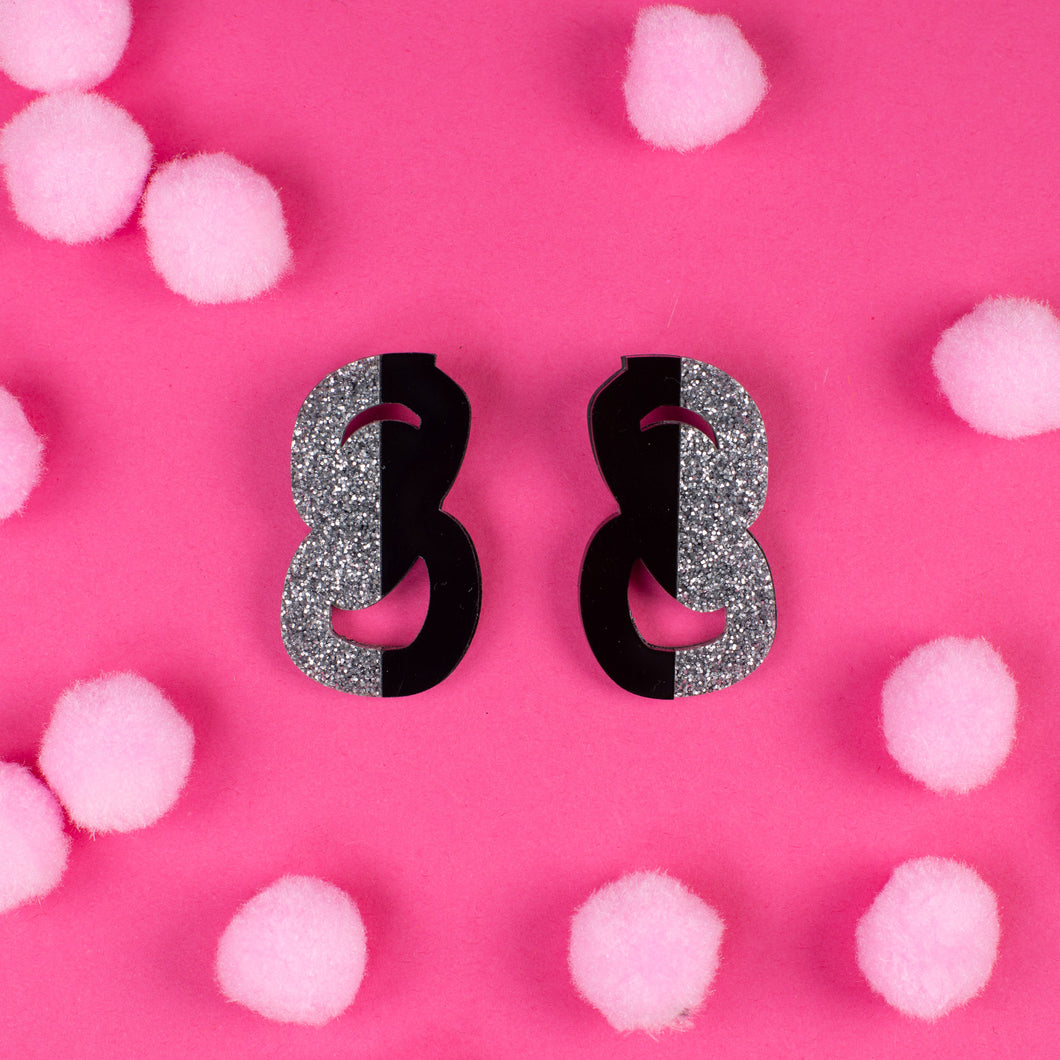 black and silver statement stud earrings on pink background