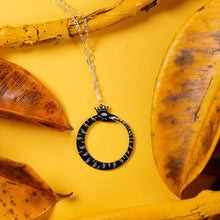 Load image into Gallery viewer, black ouroboros necklace over yellow background