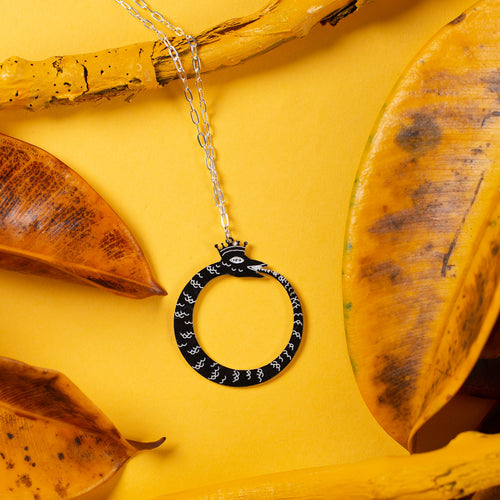 black ouroboros necklace over yellow background