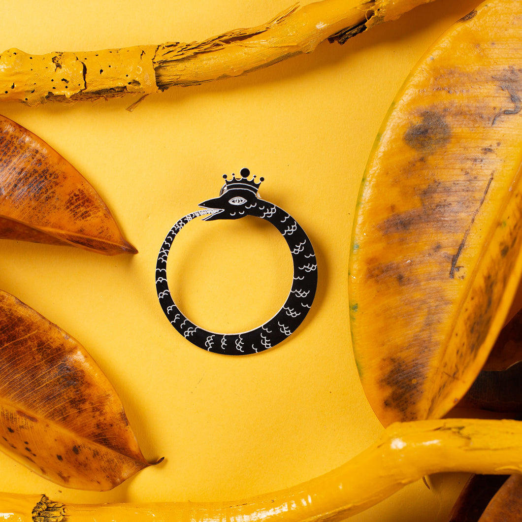 black ouroboros pin over yellow background