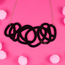 chunky black statement necklace on pink background