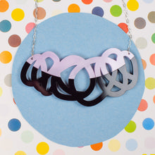 Load image into Gallery viewer, Chunky black & lilac statement necklace on polka dot background