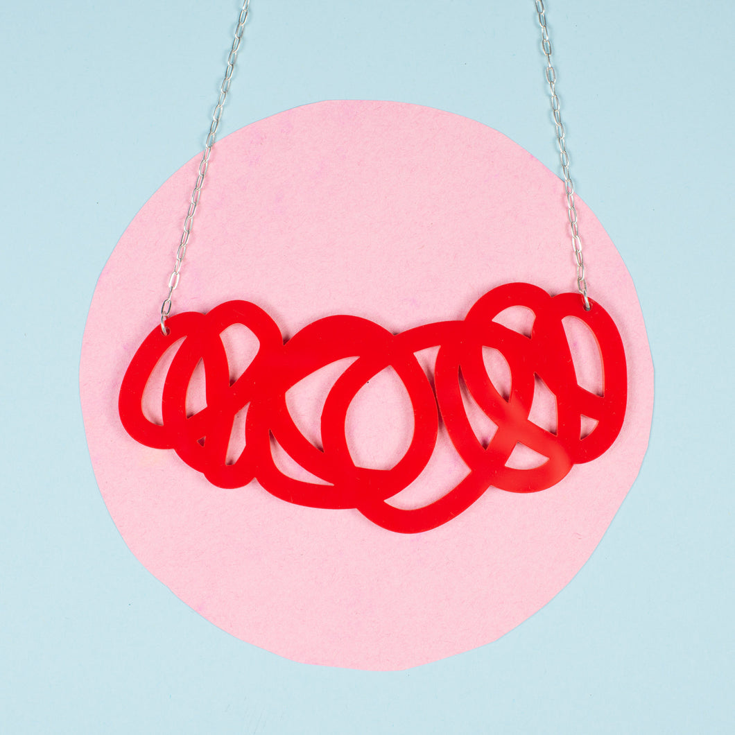 chunky red statement necklace shown over pink and blue background